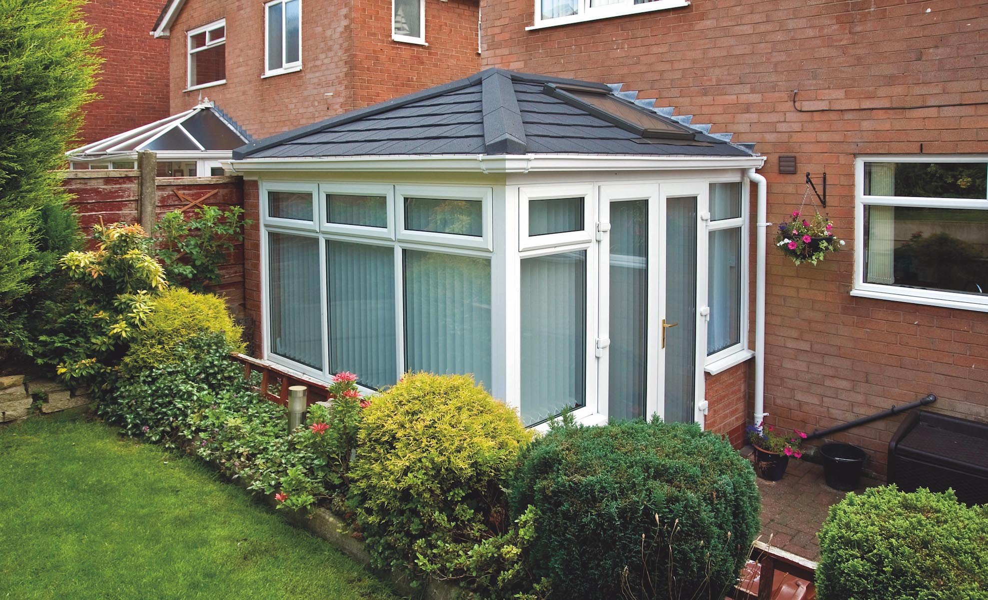 Conservatory refurbished with a Metrotile Lightweight Roof System Shingle Charcoal and Velux Window